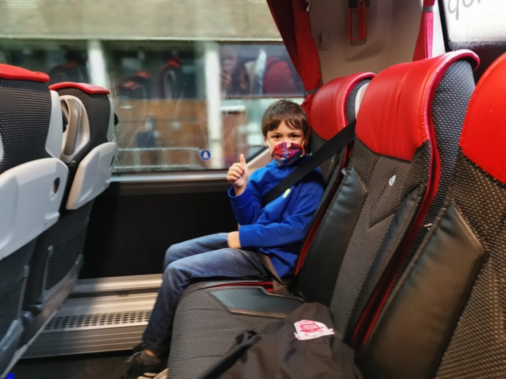 boy giving thumbs up wearing face mask on bus