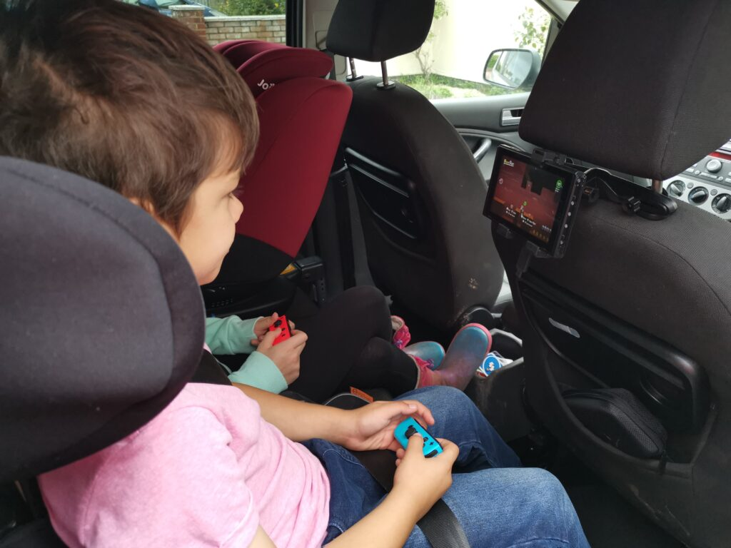 Nintendo Switch attached to headrest in car for in car entertainment