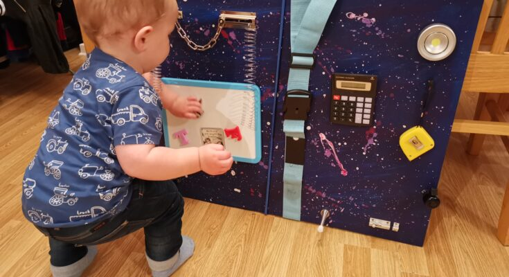 Toddler playing with busy board