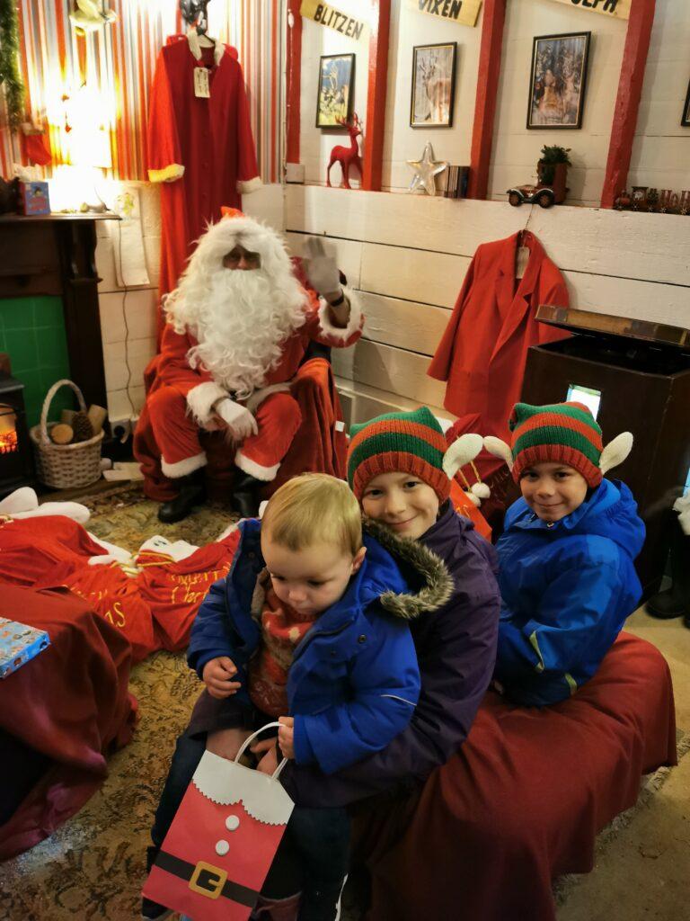 kids sat in Santa's Grotto