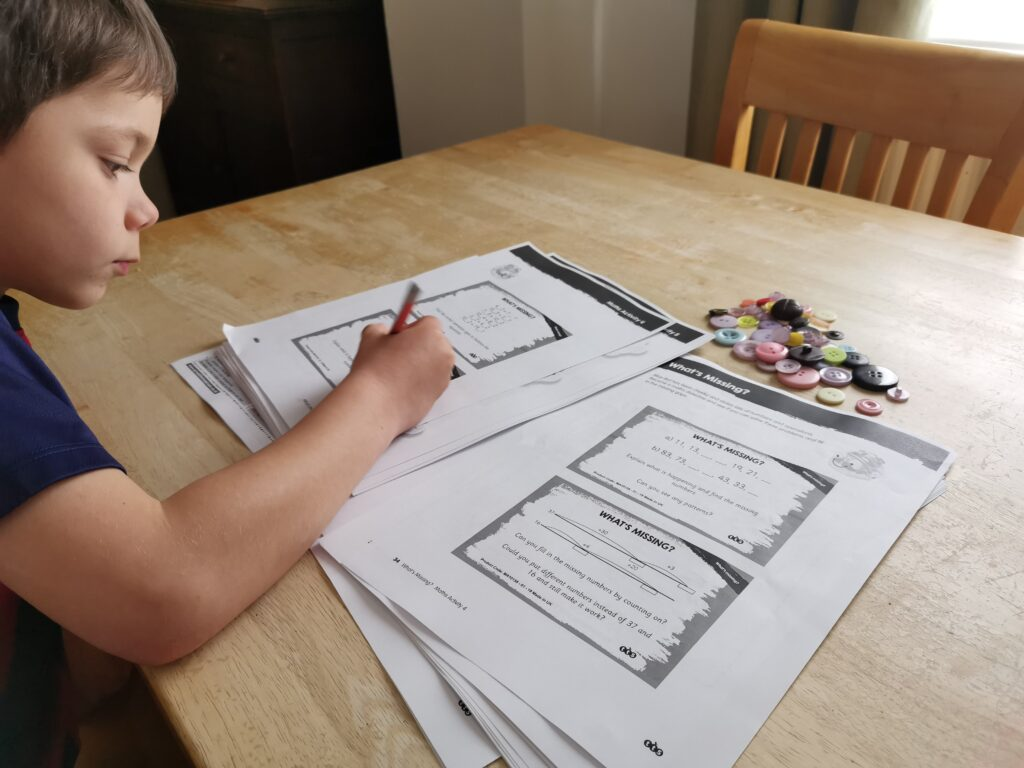 boy sat at table using buttons for math work