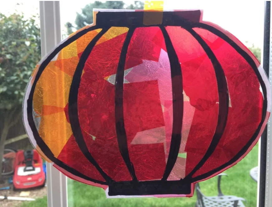 black outline of chinese lantern filled with red to make sun catcher on window