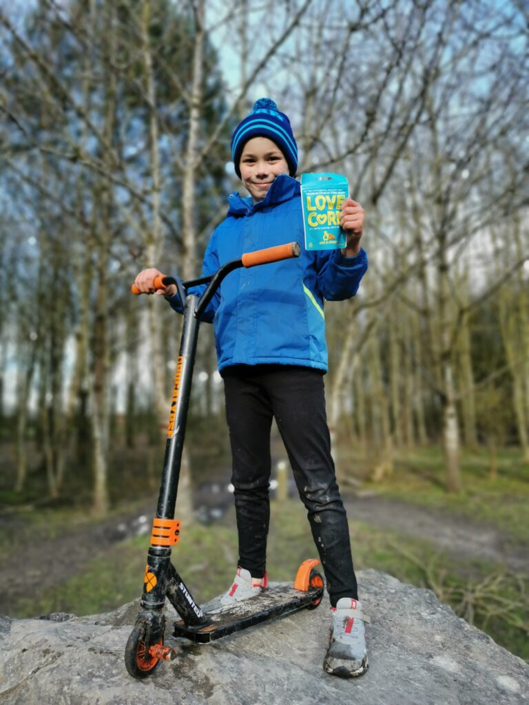 boy holding bag of Love Corn snacks with scooter stood on rock