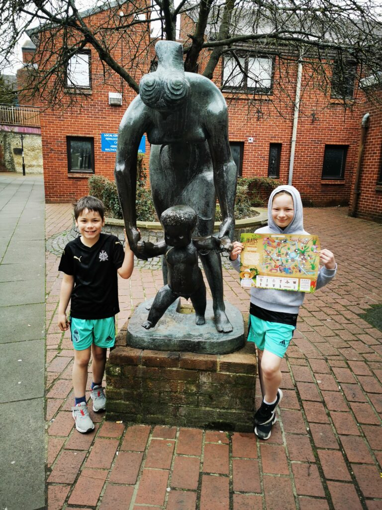 kids standing nex to statue of mother and baby