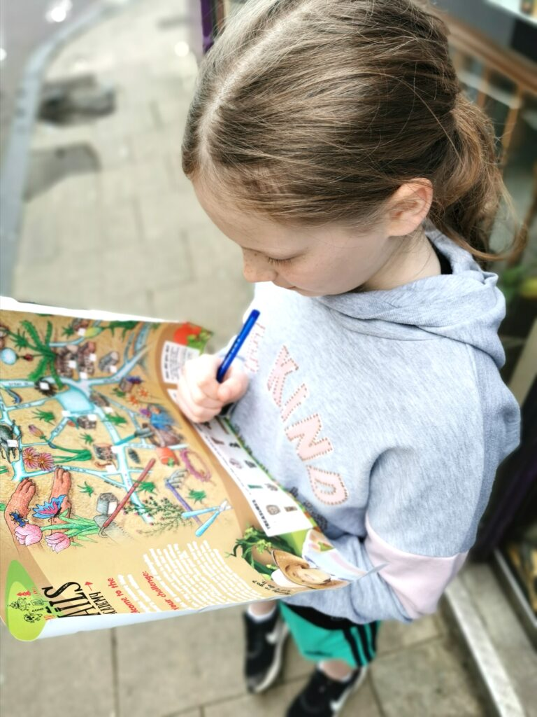 girl holding treasure map trails map