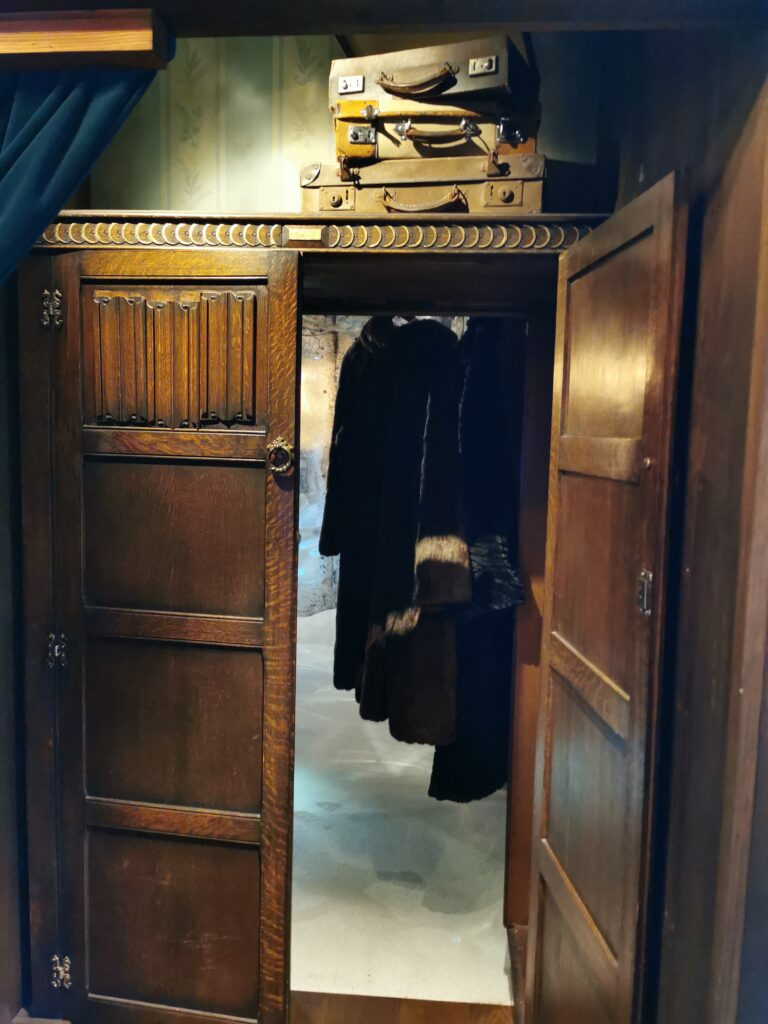 Wardrobe with fur coats hangin leading to snowy land